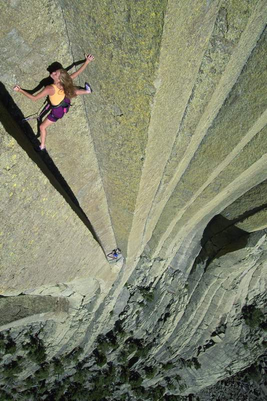 woman climbing up Devils Tower, WY