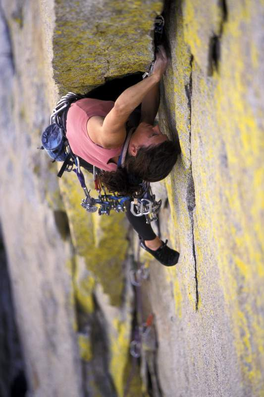 A female rock climber placing a camming device in a crack while lead climbing on a climbing route.