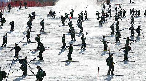Course workers carry poles after dismantling the the women's giant slalom course in Park City, Utah Friday, Feb. 22, 2002 at the Salt Lake City Winter Olympics. The women's giant slalom was the final alpine ski event in Park City at the Salt Lake City Winter Olympics. (AP Photo/Diether Endlicher)