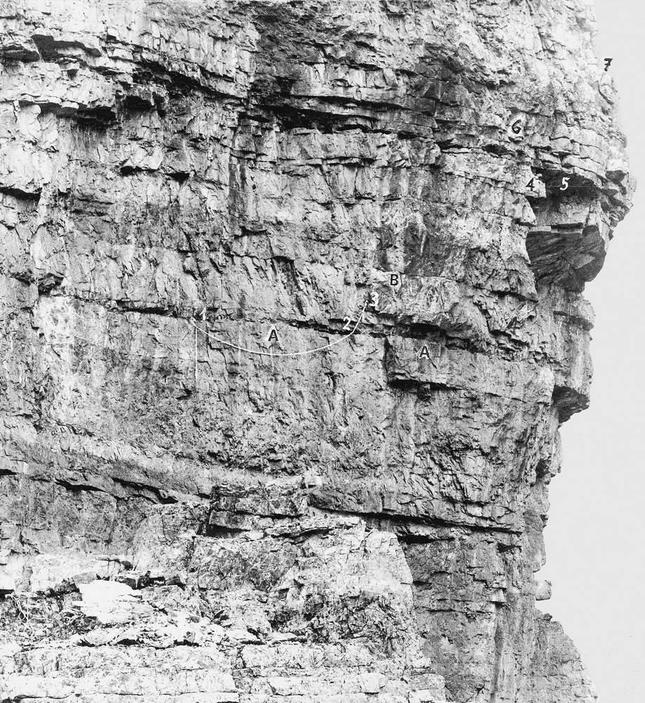 La foto ingannatrice.  Gli Strapiombi Nord del Campanile di Val Montanaia con la corda del tentativo Fanton, ripresi dal fotografo Marchetti il 23 settembre 1923, dunque due anni prima della salita Casara. La corda è attaccata a sinistra ad un chiodo (1) nella fessura orizzontale (A) e, a destra dell'arco, a tre chiodi (2) nella stessa fessura. Essa si prolunga poi in alto vicino alla fessura superiore (B), parallela a quella sottostante A, sostenuta da un quinto chiodo (3). In seguito, secondo ciò che racconta Casara, il quinto chiodo si staccò lasciando il tratto di corda pencolante dai tre chiodi (2) della fessura inferiore (A). Casara, nel 1925, trovò pertanto la fine destra della corda Fanton sui tre chiodi della fessura A, col capo pencolante dagli stessi: fessura ch'egli seguì per raggiungere lo Spigolo a Sega e poi la parete articolata e il Ballatoio, come segnò il giorno dopo in uno schizzo abbozzato nel libro del rifugio Padova. Sempre secondo la ricostruzione di Casara, pochi giorni dopo la salita, egli, avuta dal Marchetti questa foto, segnò una linea retta a destra dell'estremità della corda Fanton, che qui nella foto è meno di un metro più in alto del punto dei tre chiodi dai quali pendeva la corda all'atto della salita. In tal modo, ingannato dalla foto che faceva finire la corda verso la fessura alta (B) egli segnò questa quale passaggio anziché quella bassa (A) dove finiva la corda quando egli salì. 4-4 =Spigolo a Sega. 5=Tetto. 6=Gibbosità. 7=Appoggio. Foto: Arnaldo Marchetti.