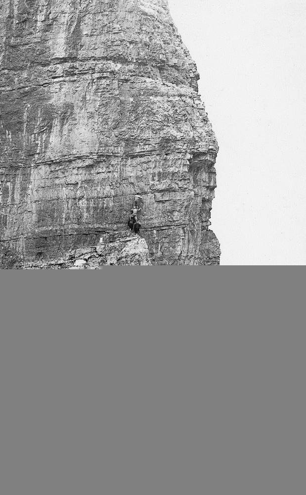 Attilio Tissi, in bilico sulla piramide formata dai compagni, raggiunge il gruppo chiodi Fanton.