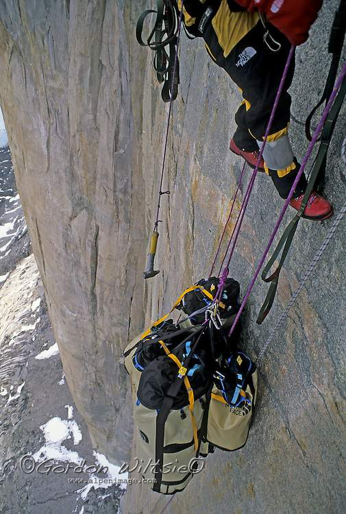 BAFFIN ISLAND, NUNAVUT, CANADA. A rock climbing expedition prepares to lower huge haul bags that are used to drag food, water and equipment up a big wall climb. This load was so heavy that the friction generated by a braking device almost melted the rope.